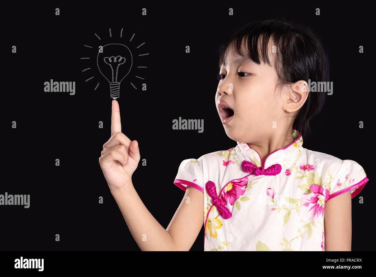 Asian chinese little girl pointing finger up to bulb in isolated black background - Stock Image