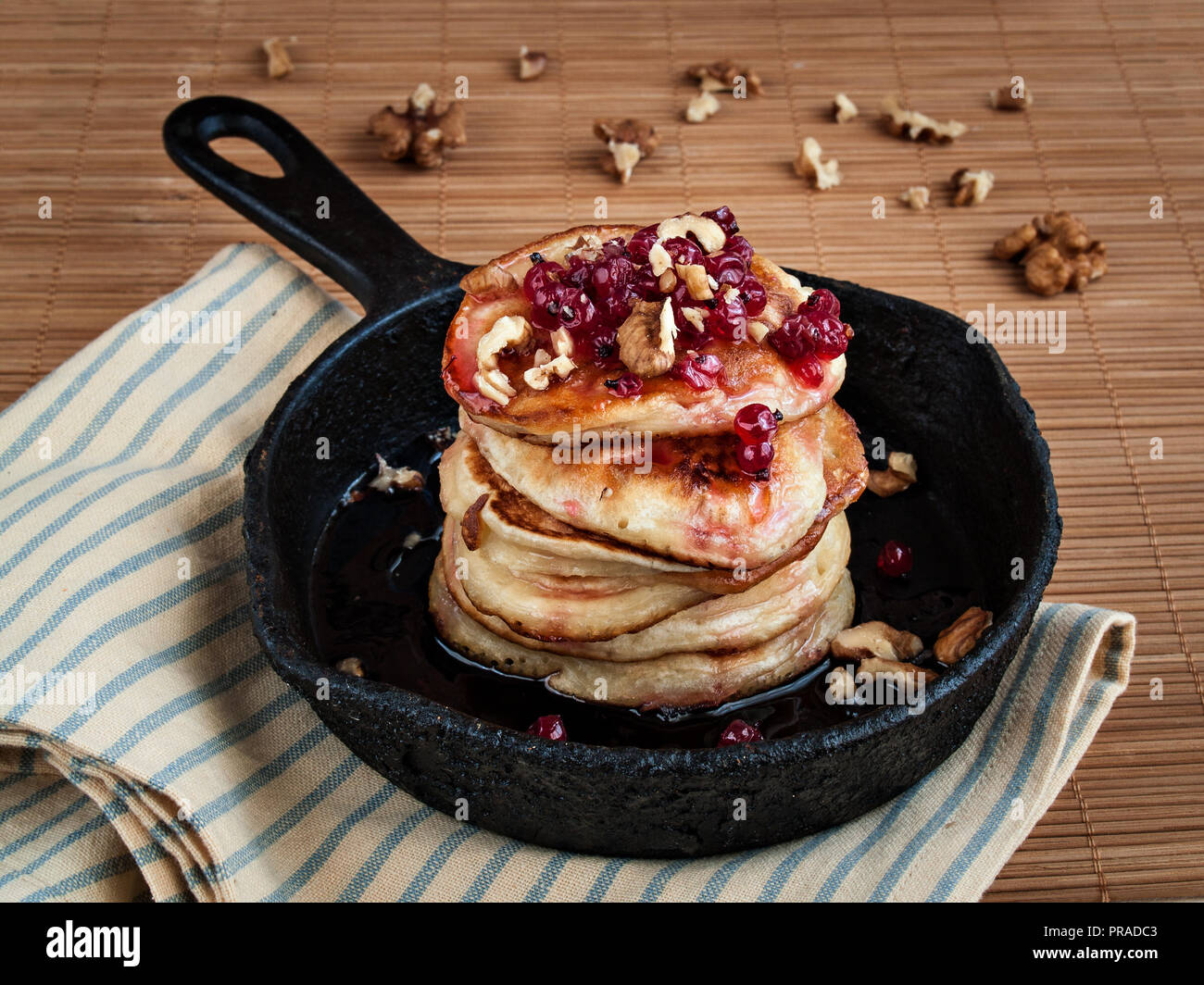 Ruddy delicious pancakes lie in a cast-iron frying pan poured with currant jam and sprinkled with walnut Stock Photo