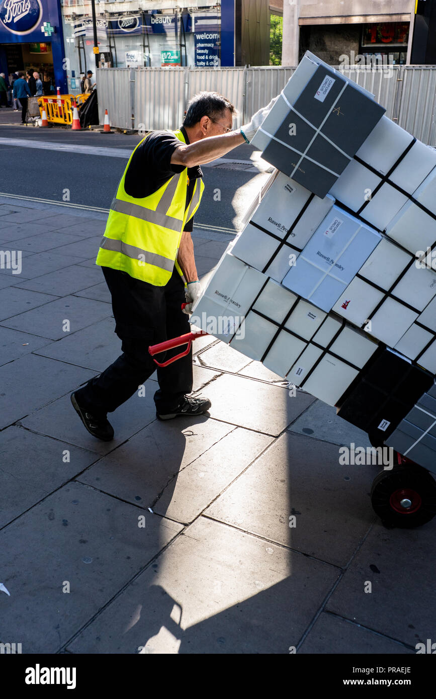 Delivery man with heavy load. Oxford Street, London, UK - Stock Image