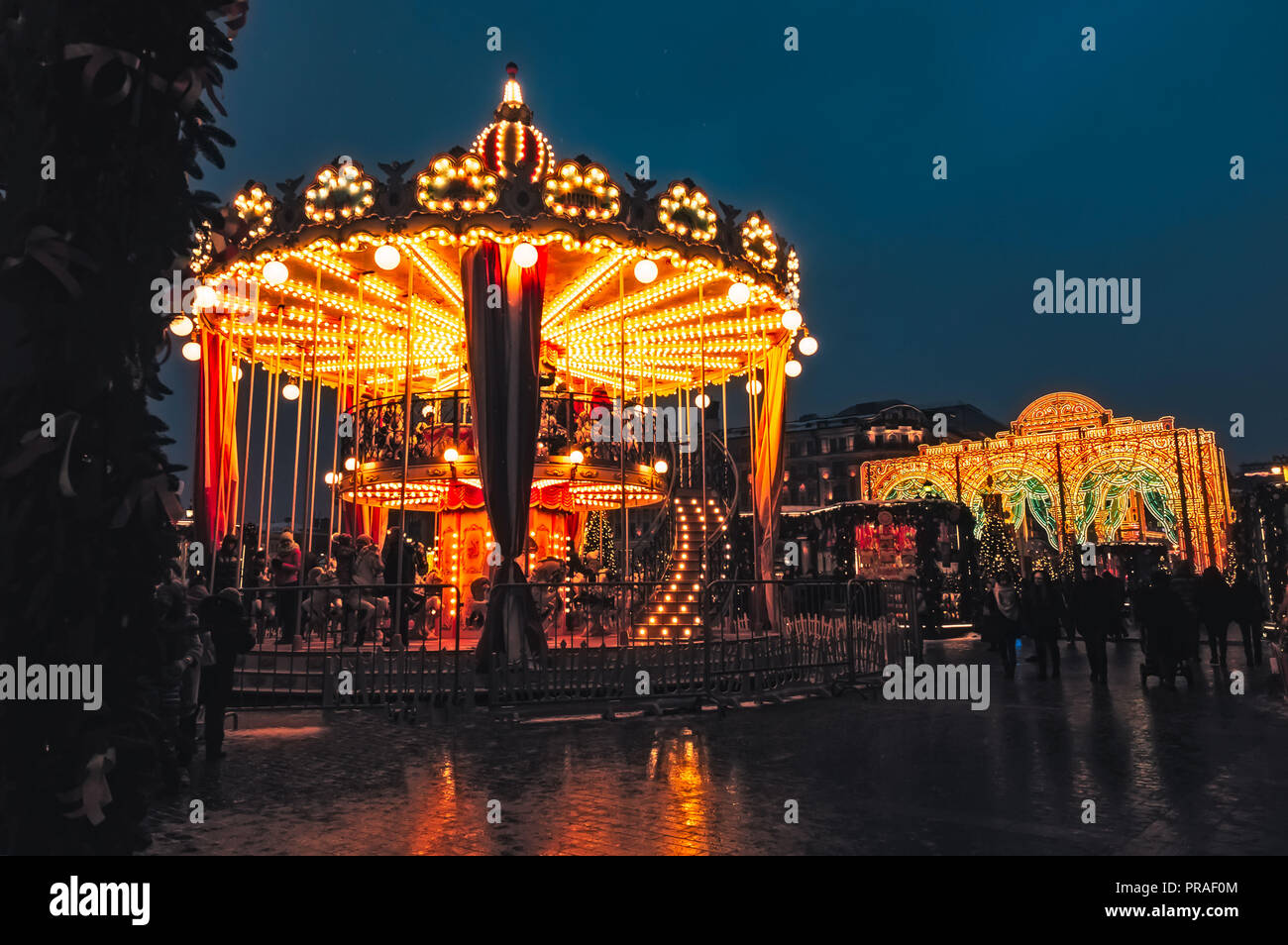 People on carousel near Red Square decorated and arranged for Christmas New Year. Christmas fair. Luminous roundabout rotates with adults and children - Stock Image