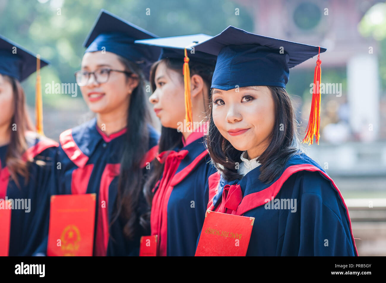 Hanoi, Vietnam - October 16, 2016. Group of students dressed in caps and gowns celebrating their university graduation. Temple of Literature. - Stock Image