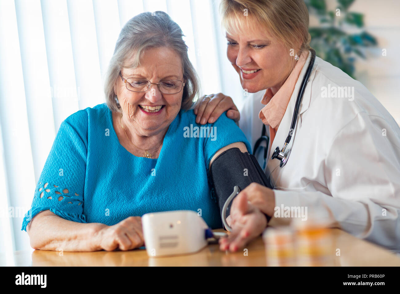 Senior Adult Woman Learning From Female Doctor to Use Blood Pressure Machine. - Stock Image