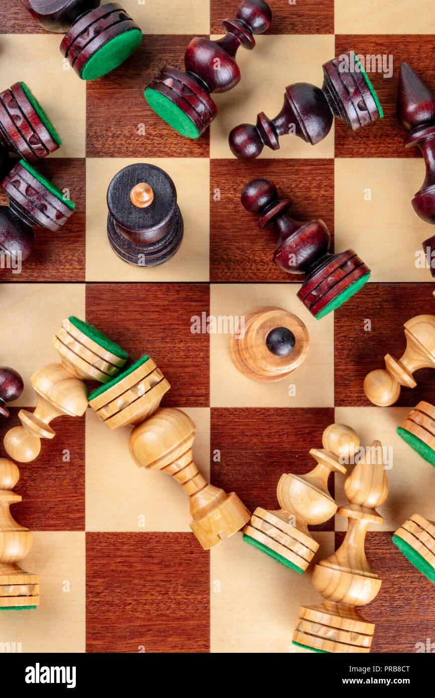 An overhead photo of a checkmate situation in chess with nearly all the pieces fallen on the chessboard - Stock Image