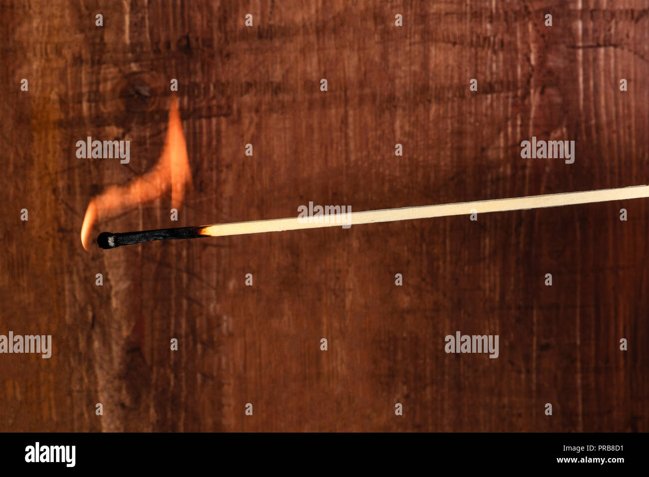 A side view of a burning match on a dark rustic background with copy space - Stock Image