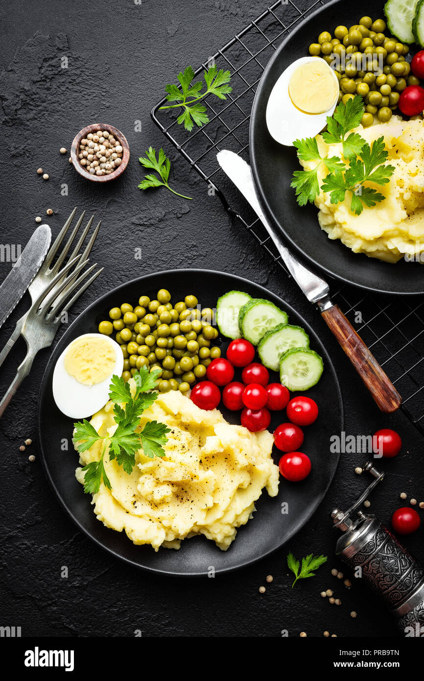 Mashed potato with green peas, tomatoes, cucumber and boiled egg. Potato puree on plate with vegetables and egg Stock Photo
