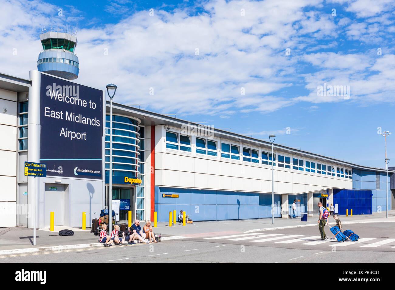 East Midlands Airport Passengers heading towards the departures entrance east midlands airport terminal building Castle Donnington Leicestershire UK - Stock Image