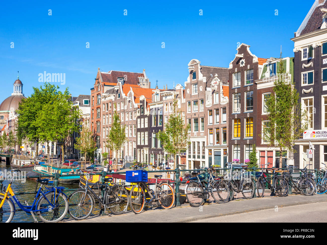 Amsterdam houses and bikes on Singel an Amsterdam canal Blauwburgwal bridge over Singel canal amsterdam bicycle propped against railings Amsterdam EU - Stock Image