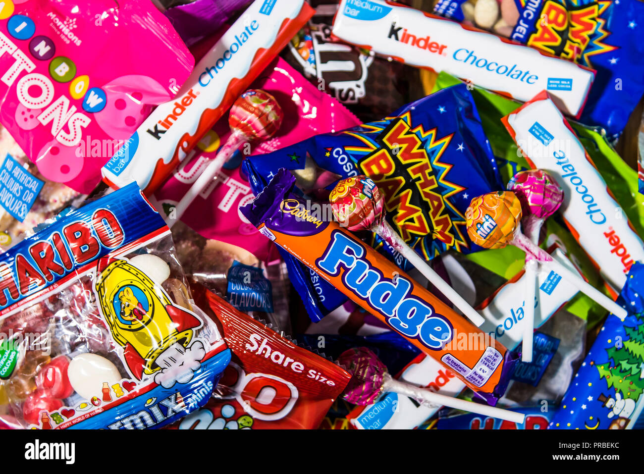 Assorted candy chocolate bars and sweets in brightly coloured wrappers. - Stock Image