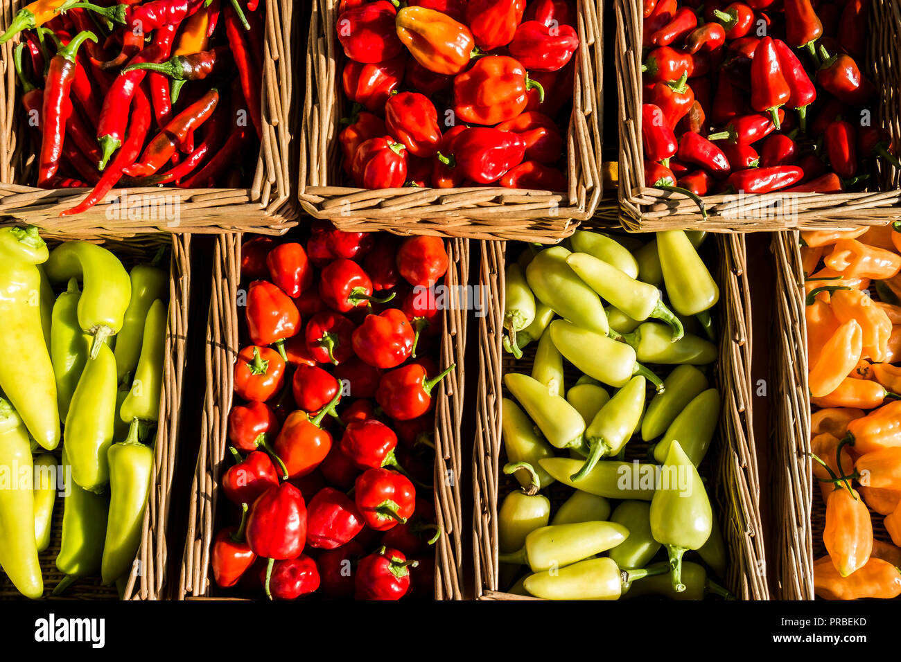 A variety of fresh chillies on a market stall. - Stock Image