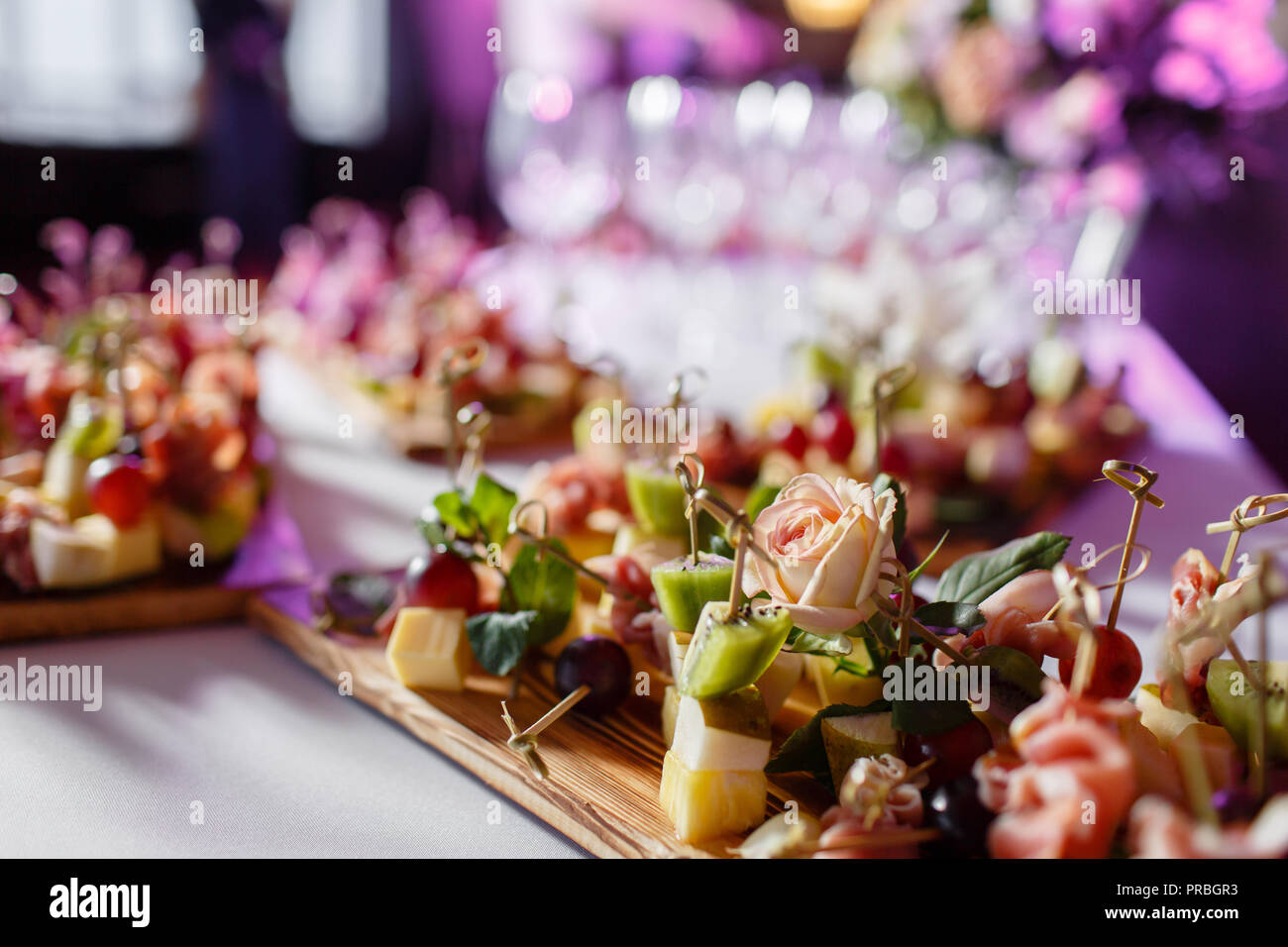 the buffet at the reception. Assortment of canapes on wooden board. Banquet service. catering food, snacks with cheese, jamon, prosciutto and fruit - Stock Image