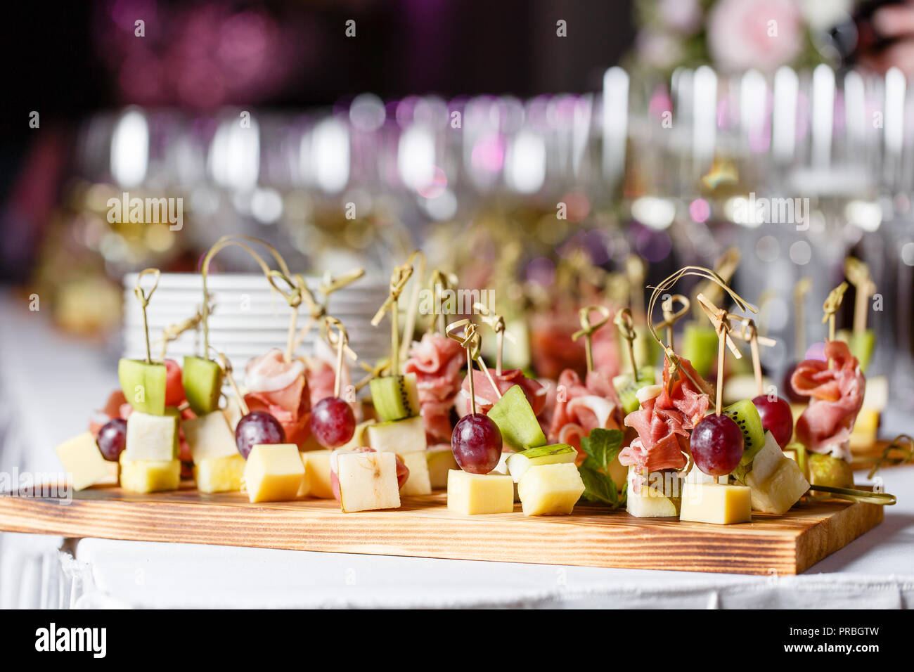 the buffet at the reception. Glasses of wine and champagne. Assortment of canapes on wooden board. Banquet service. catering food, snacks with cheese, jamon, prosciutto and fruit - Stock Image