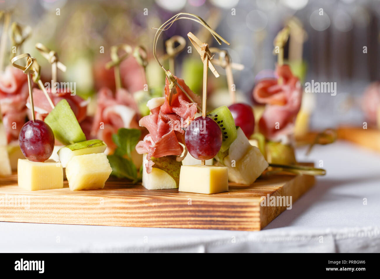 Light snacks in a plate on a buffet table. Assorted mini canapes, delicacies and snacks, restaurant food at event. A gala reception. Decorated delicious table for a party goodies. - Stock Image