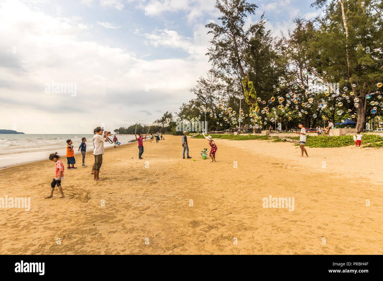 Visitors playing with soap bubbles while enjoying a day on Tanjung Aru Beach Kota Kinabalu Sabah Malaysia Borneo - Stock Image