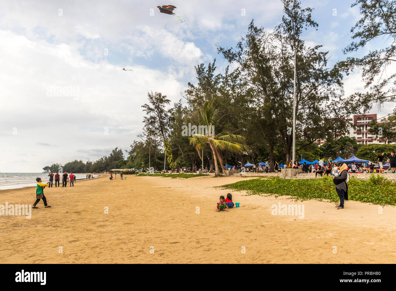 Visitors and tourist enjoying a day on Tanjung Aru Beach Kota Kinabalu Sabah Malaysia Borneo - Stock Image