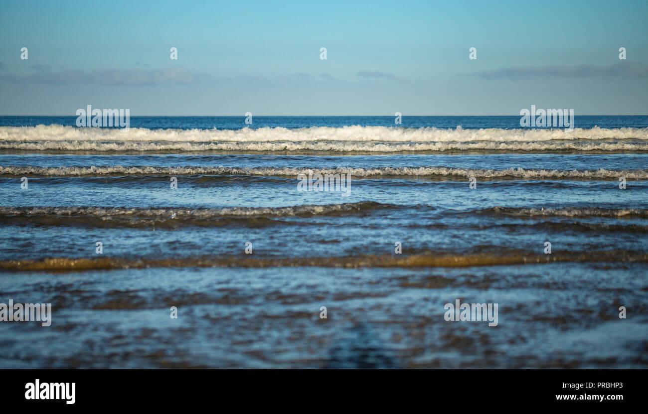 Long blue tidal waves crashing in morning light  Newgale Beach in