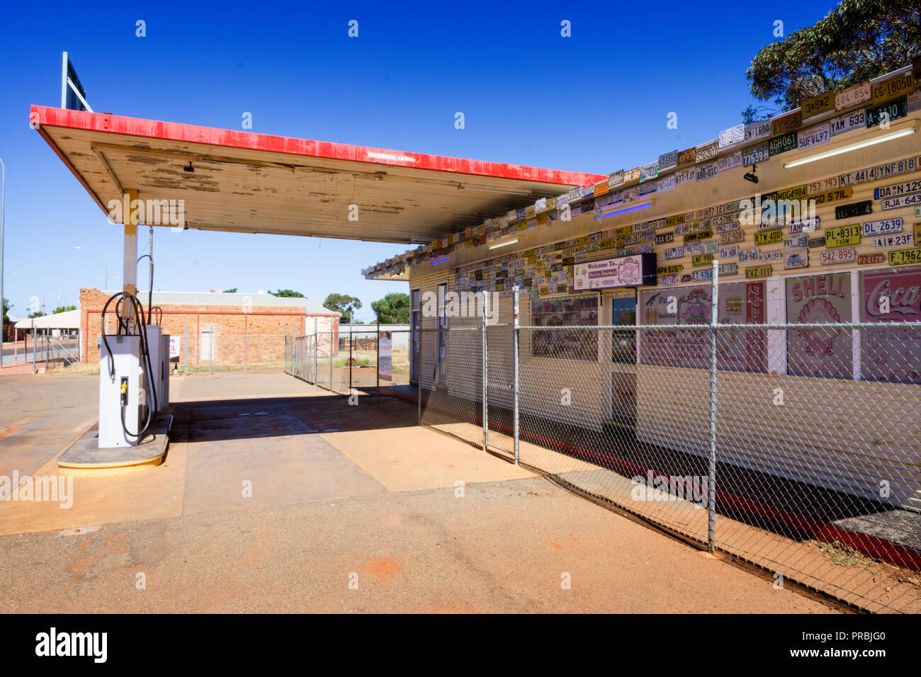The disused Menzies roadhouse is decorated with number plates and is serviced by 24 hour automatic fuel pumps, Menzies Western Australia - Stock Image