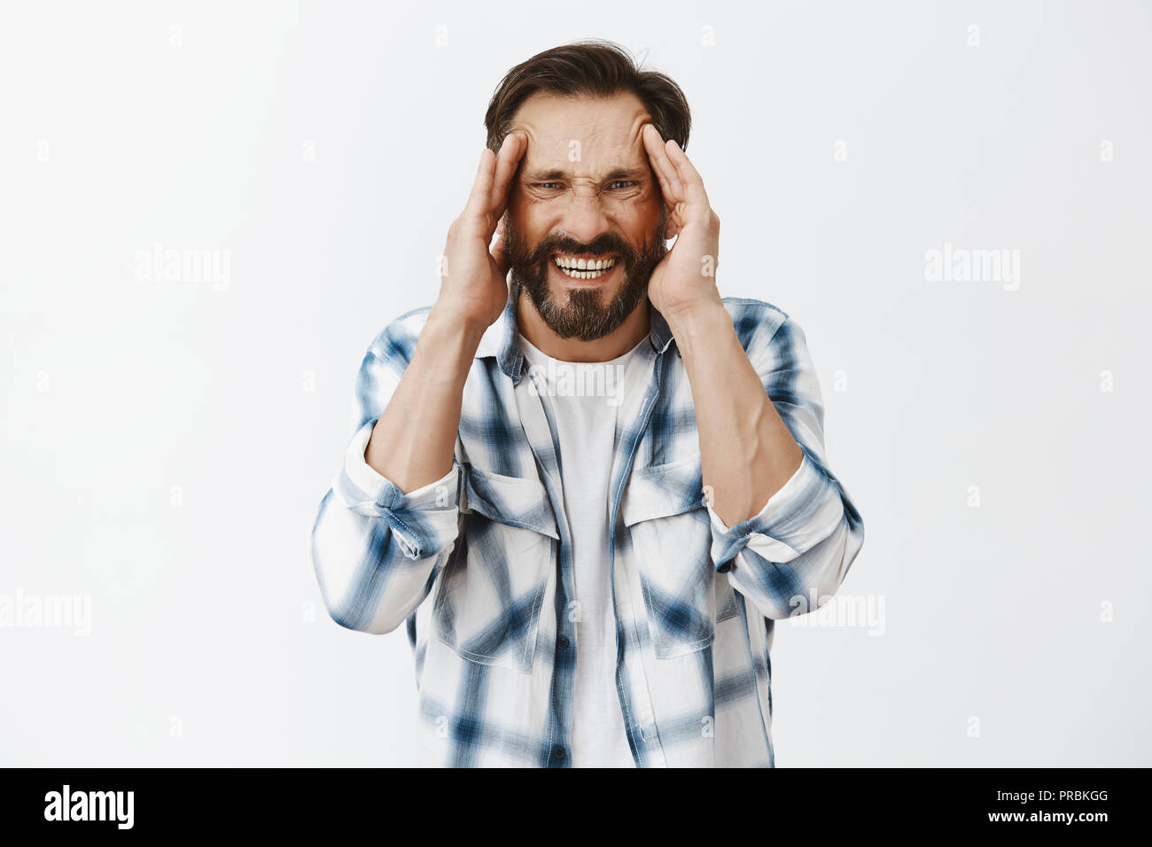 Turn pain off please. Distressed adult bearded guy suffering from painful migraine or headache, grimacing from discomfort, holding hands on temples and staring with unhappy upset look at camera - Stock Image