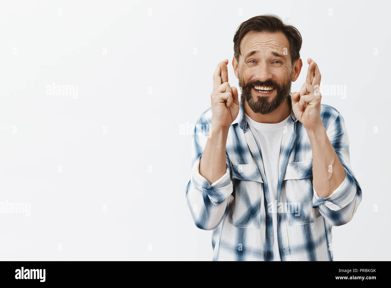Fingers crossed for good luck. Portrait of nervous charming adult caucasian man in checked shirt, praying or making wish with worried believer face, standing hopeful over gray background - Stock Image