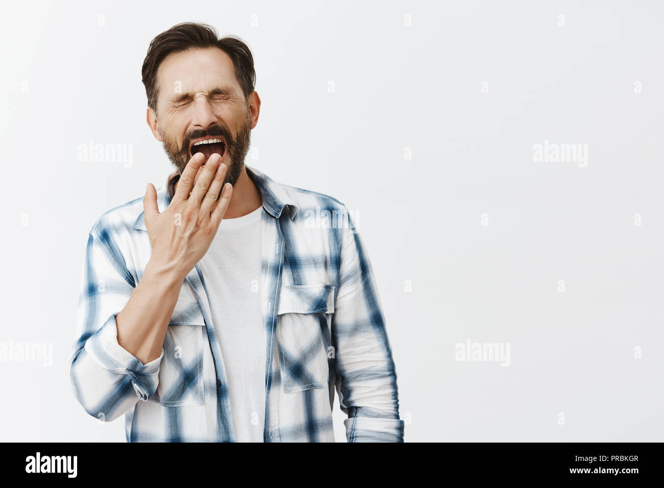 Man woke up early not be late on work, feeling sleepy and tired, standing over gray background in casual checked shirt, yawning with closed eyes and covering opened mouth with palm - Stock Image