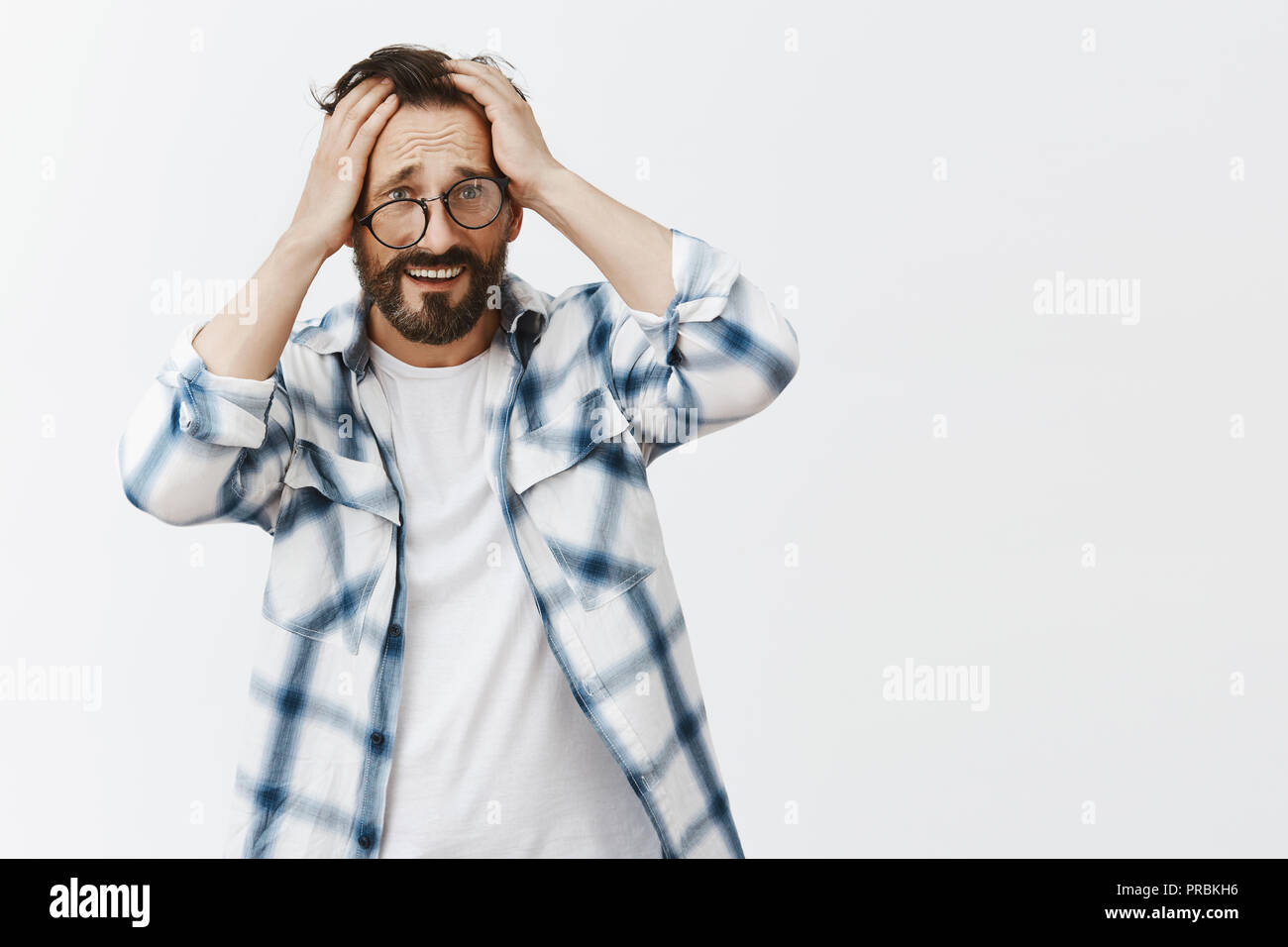 Man cannot remember how he got home after party, standing in crooked glasses, touching head and frowning, feeling headache from hangover, standing unhappy and gloomy over gray background Stock Photo