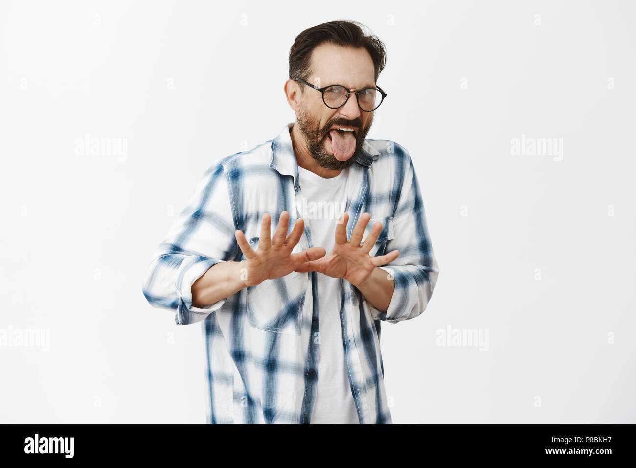 Hate vegetables, get it away from me. Portrait of disgusted and dispelased attractive european adult man in glasses, sticking out tongue, stooping and gesturing with palms, rejecting and saying no - Stock Image
