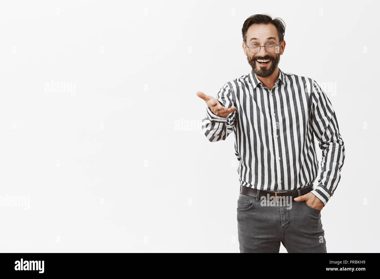 Friend, long time no see. Portrait of pleased surprised handsome adult european in striped shirt and formal pants, pointing with palm at camera and smiling broadly, greeting familiar person on meeting - Stock Image