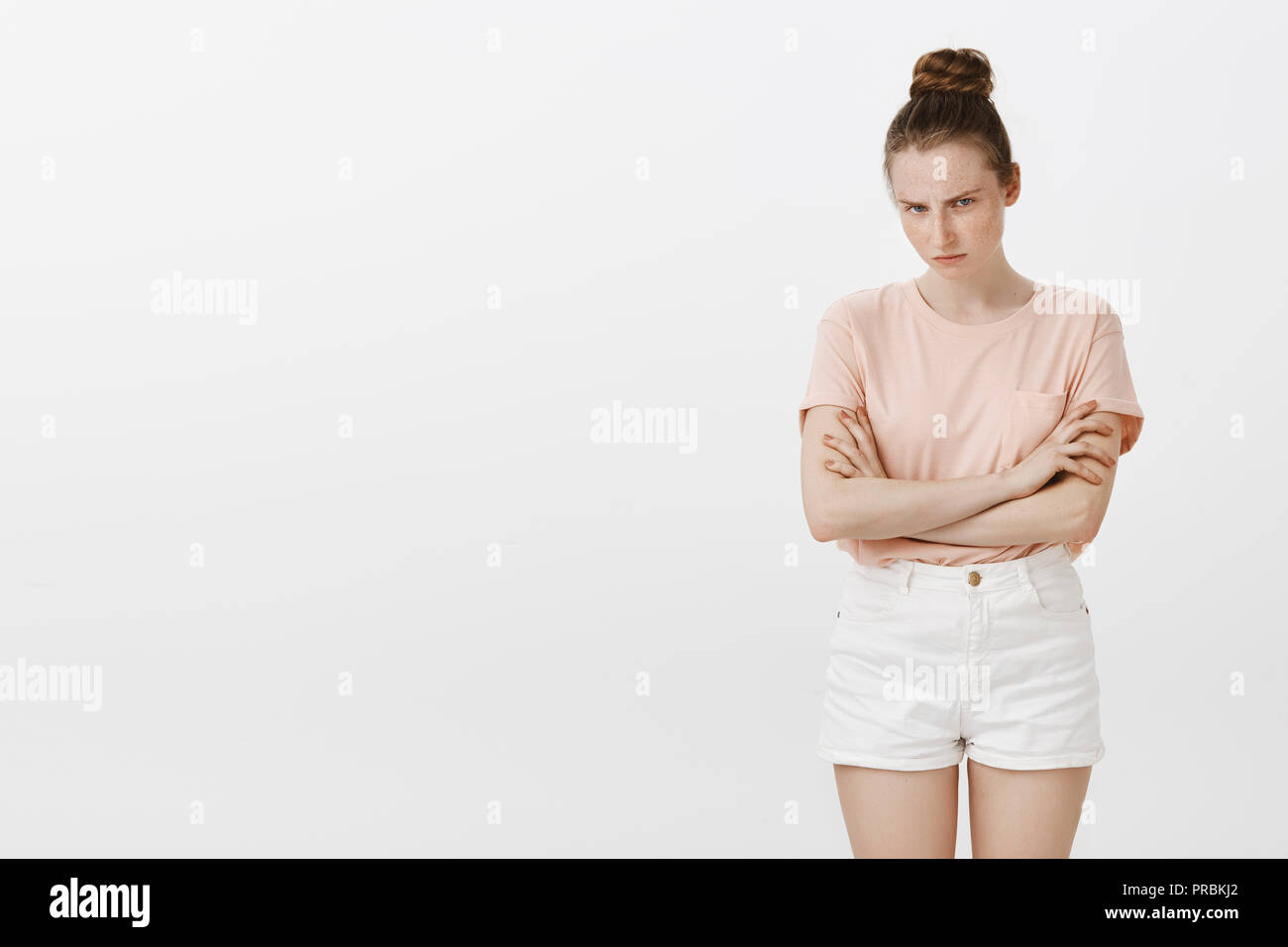 Cute girl feeling mad friend ate last cookie. Displeased angry woman with stylish bun hairstyle, looking from under forehead and frowning with evil expression, holding hands crossed over chest - Stock Image