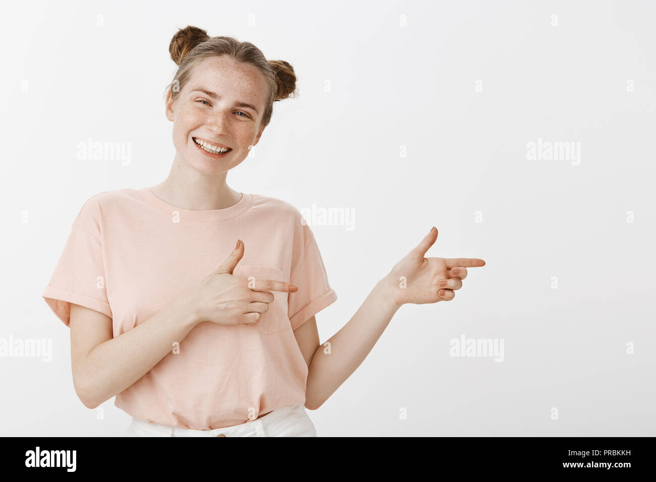 c65974e36 Studio shot of optimistic happy feminine european woman with cute buns  hairstyle and freckles, pointing