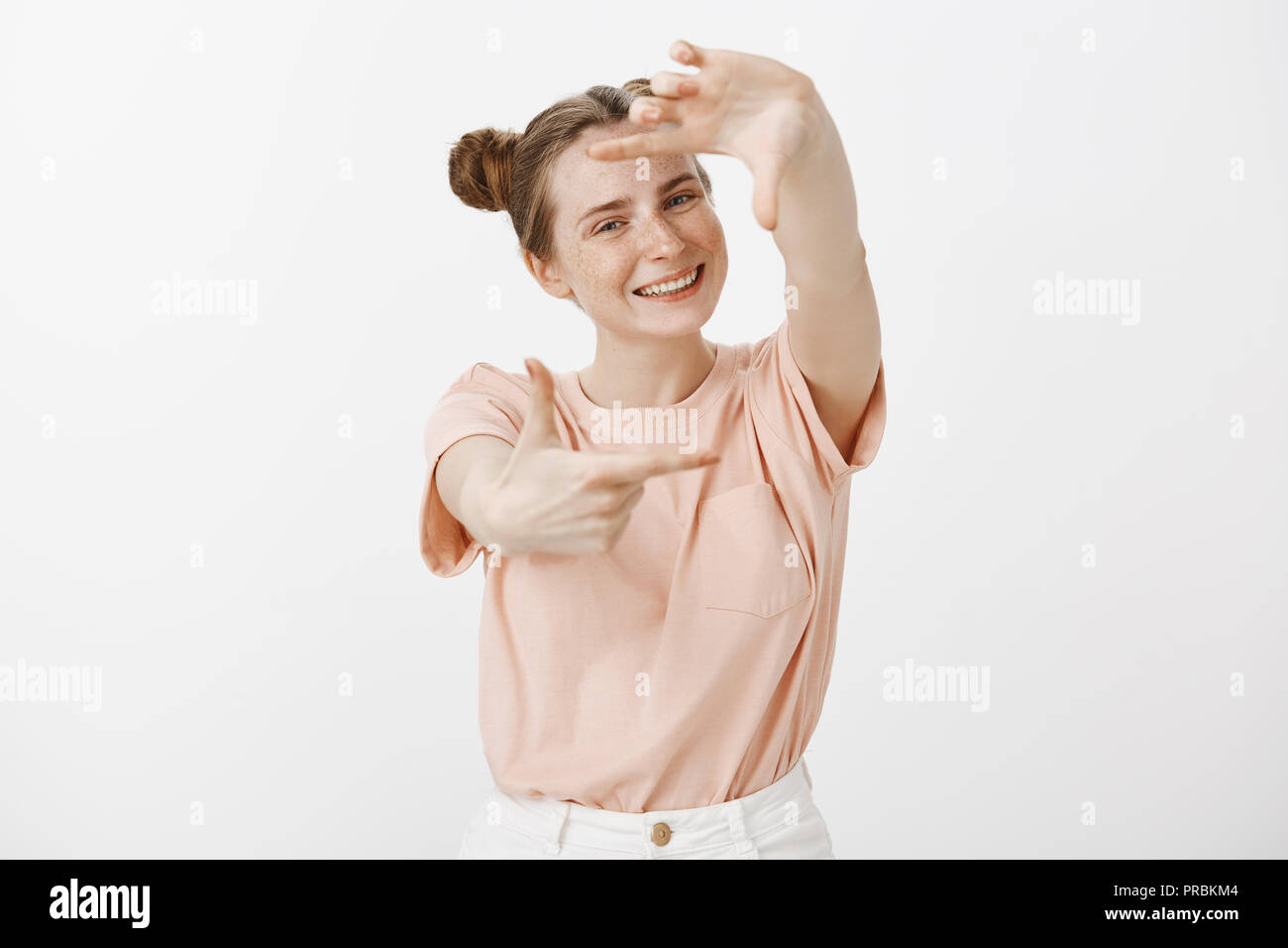 Carefree Stylish Feminine Girl With Buns Hairstyle In Trendy Clothes