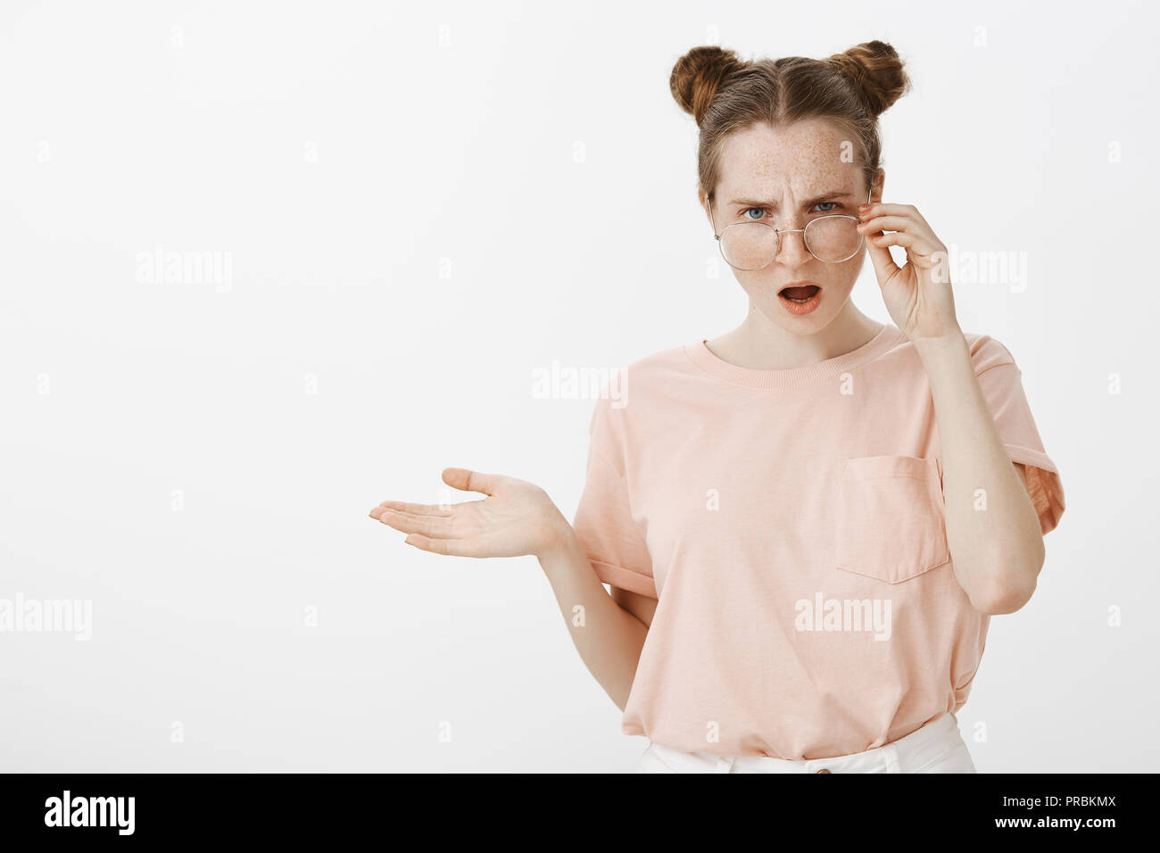 Girl hearing nonsense, having argument, being displeased what she hears. Intense puzzled girlfriend in trendy clothes, taking off eyewear, gesturing lifted palm in clueless expression, confused - Stock Image