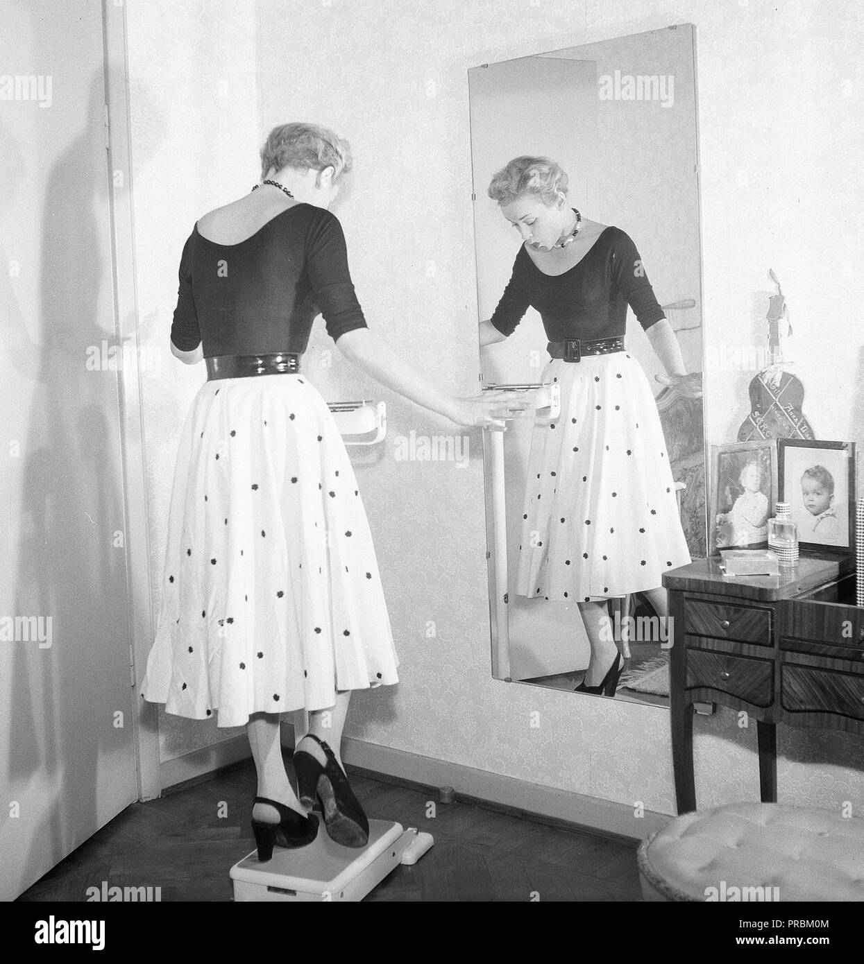 1950s fashion. A young woman is standing on one leg on the scale trying to be as light as possible. Pictures actress AnnaLisa Ericson, 1913-1911.  Sweden 1950s. Photo Kristoffersson ref BM74-10 - Stock Image
