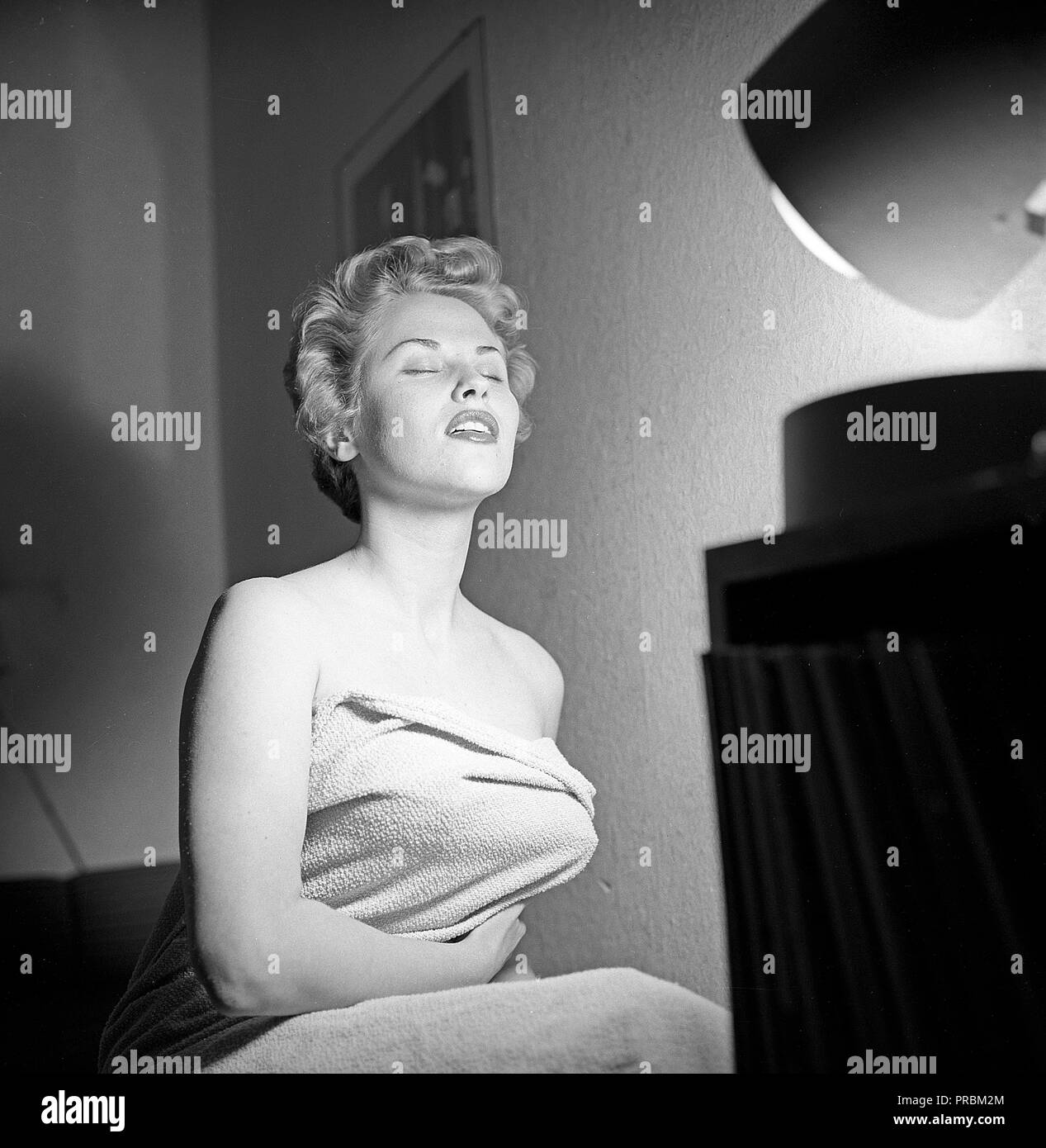 Beauty care in the 1950s  A young woman is getting a tan by