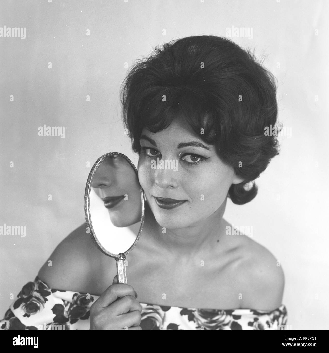 Makeup in the 1950s. A young woman is holding a makeup mirror close to her face. Sweden March 1959 - Stock Image