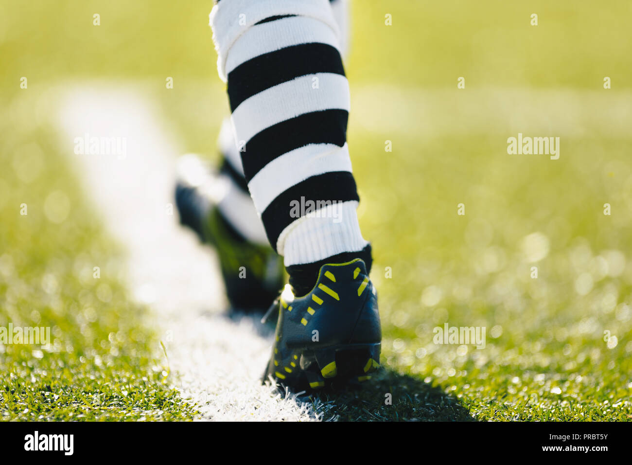 Legs of a soccer player. Football player on a grass pitch. Soccer player in professional football boots cleats and striped soccer socks - Stock Image
