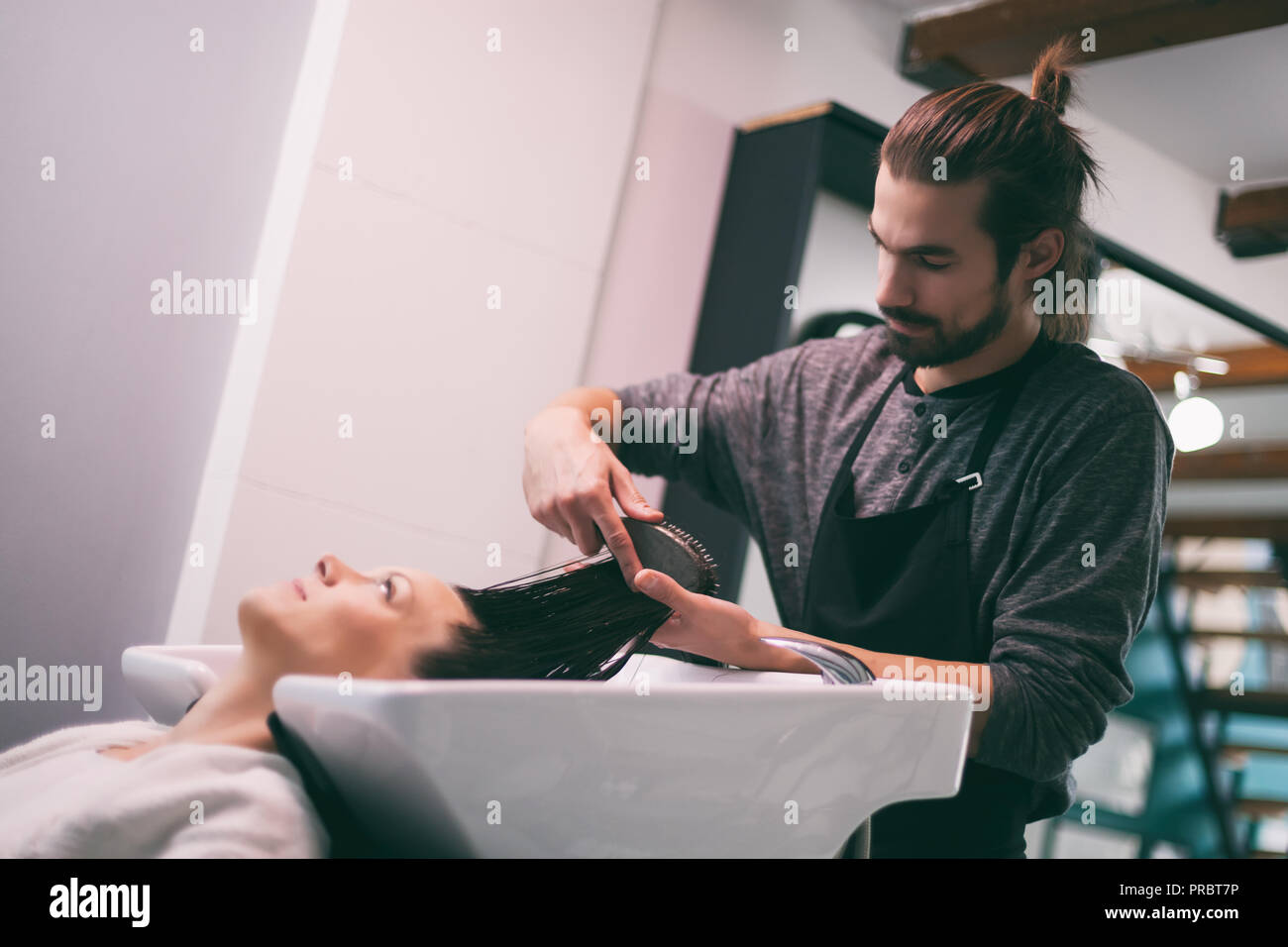 Young woman getting new hairstyle at professional hair styling saloon. - Stock Image