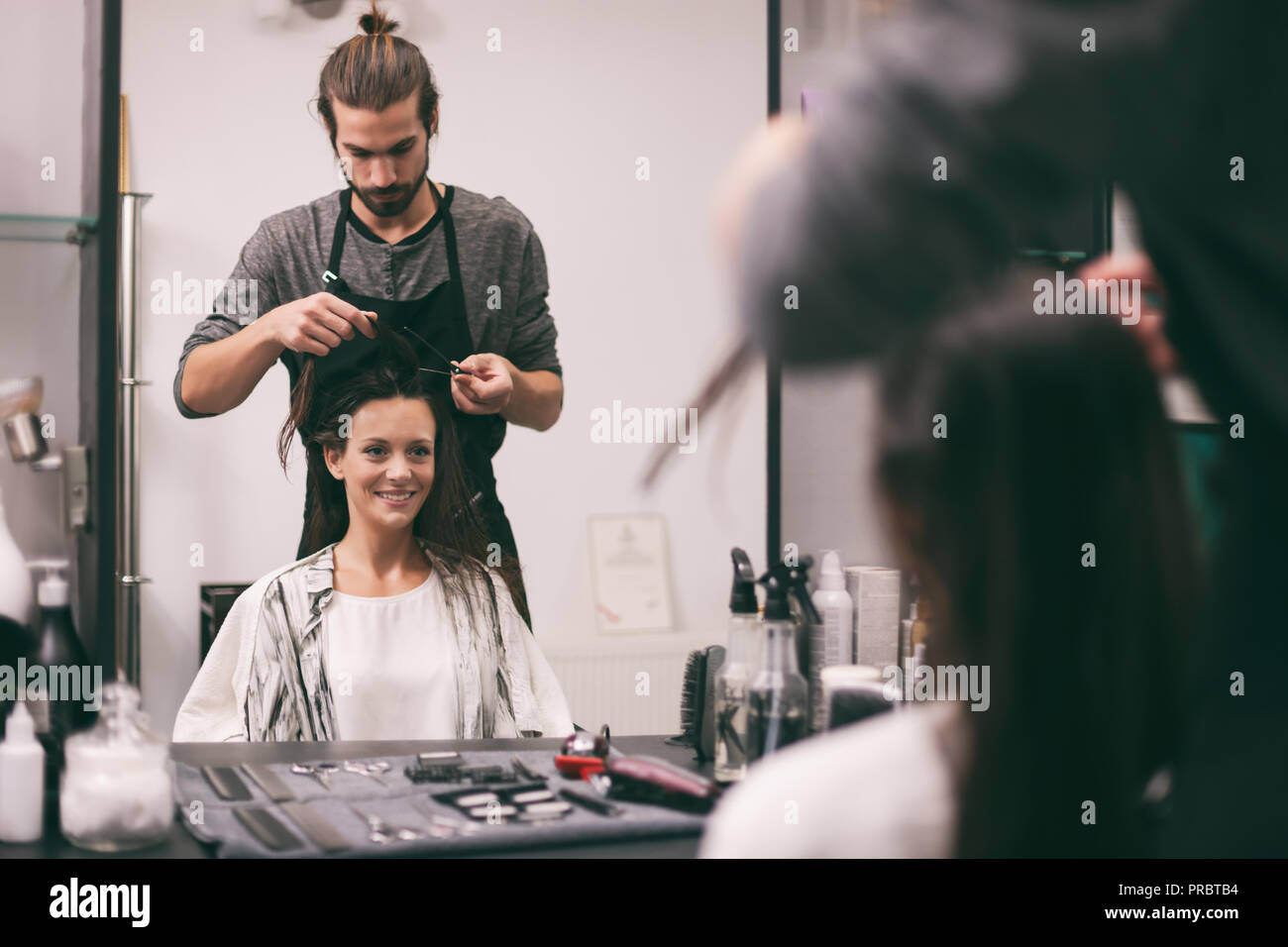 Young woman getting new hairstyle at professional hair styling saloon. Stock Photo