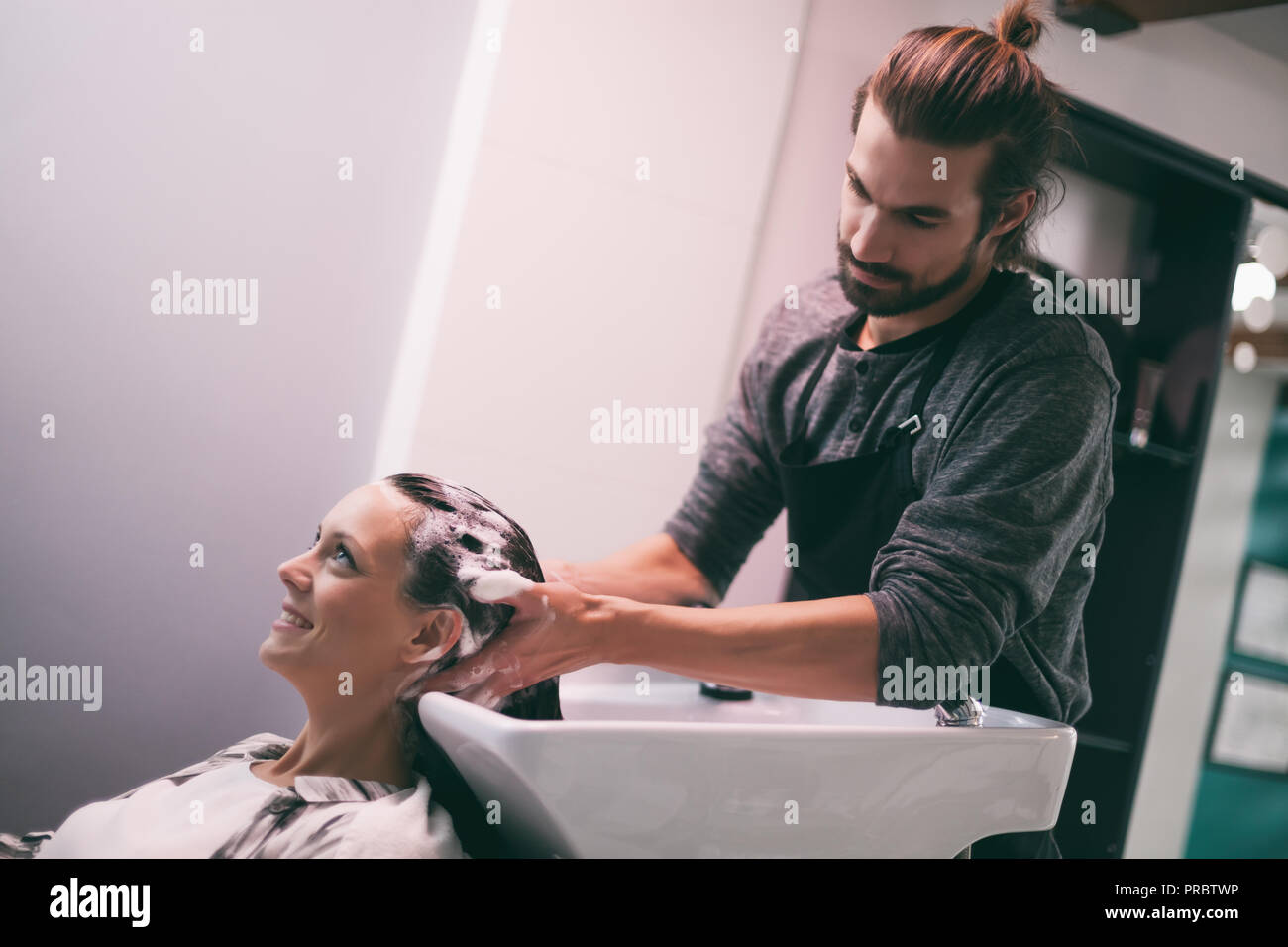 Young woman getting new hairstyle at professional hair styling saloon. Hairdresser is massaging her head. Stock Photo
