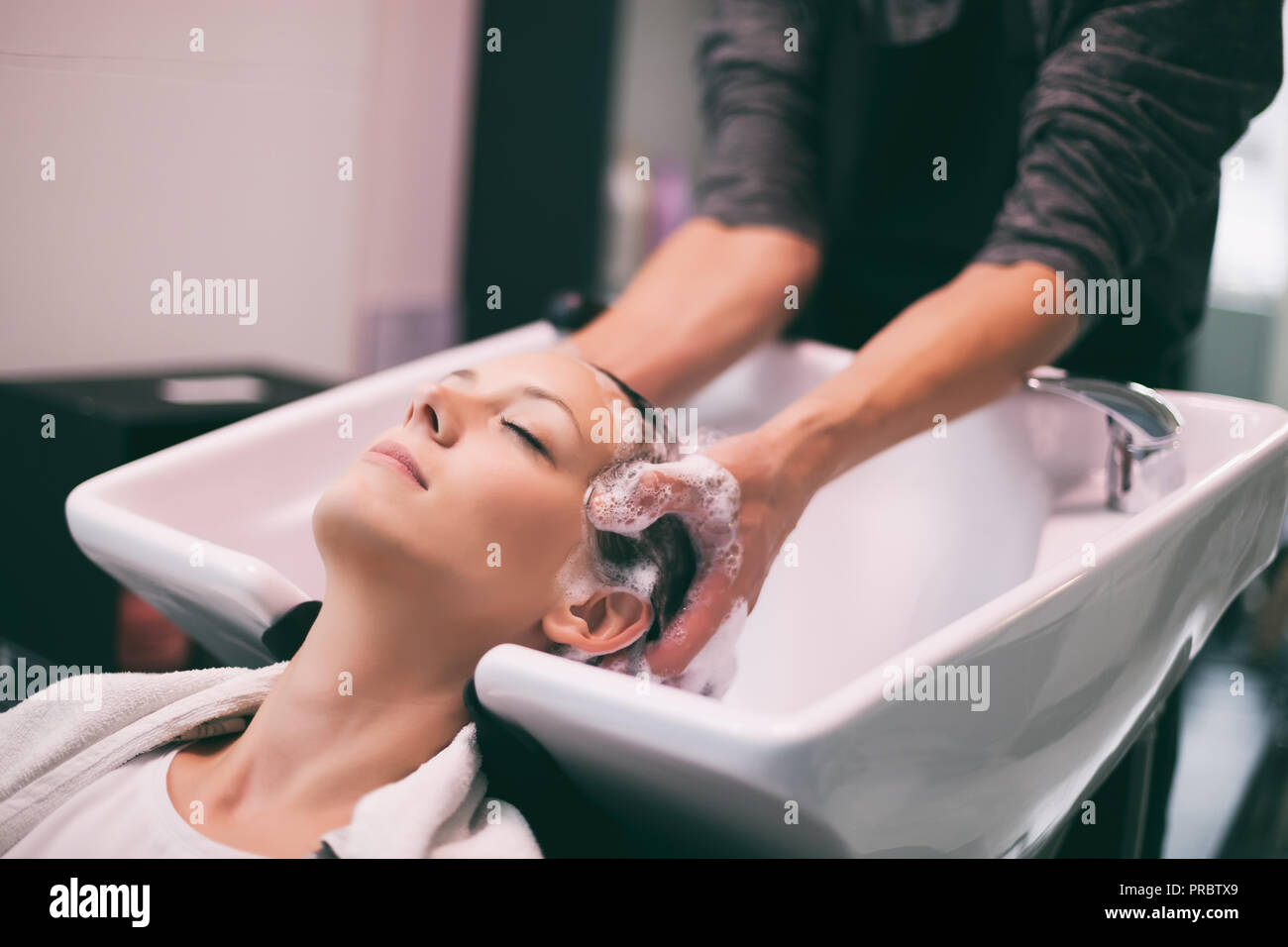 Young woman getting new hairstyle at professional hair styling saloon. Hairdresser is massaging her head. - Stock Image