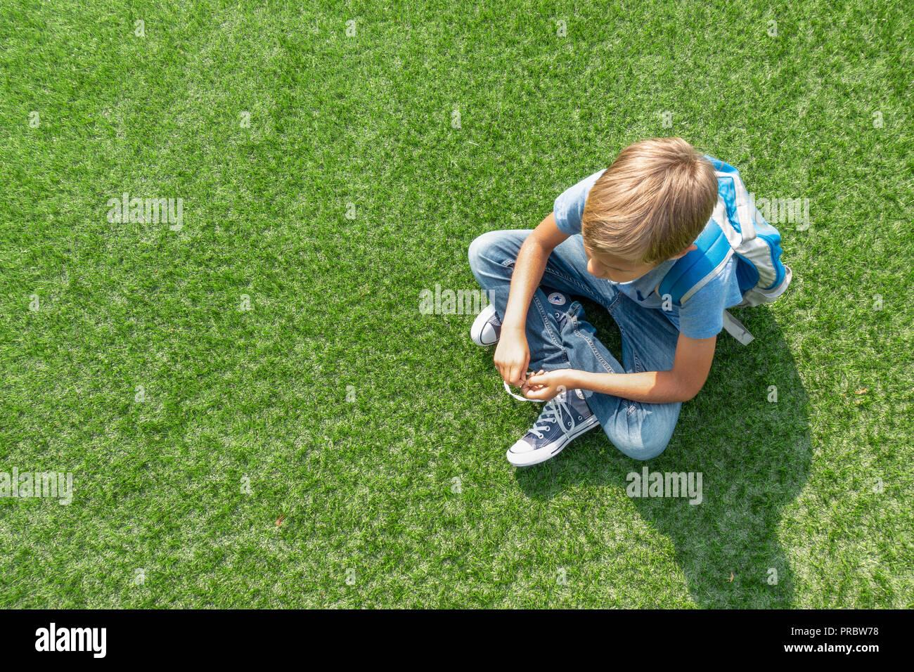 Unhappy sad upset boy sitting alone on the grass - Stock Image