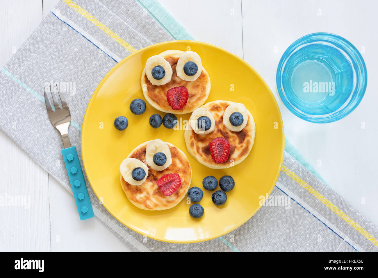 Breakfast pancakes for kids. Funny cute animal shaped pancakes on a yellow plate. Top view. Food art - Stock Image