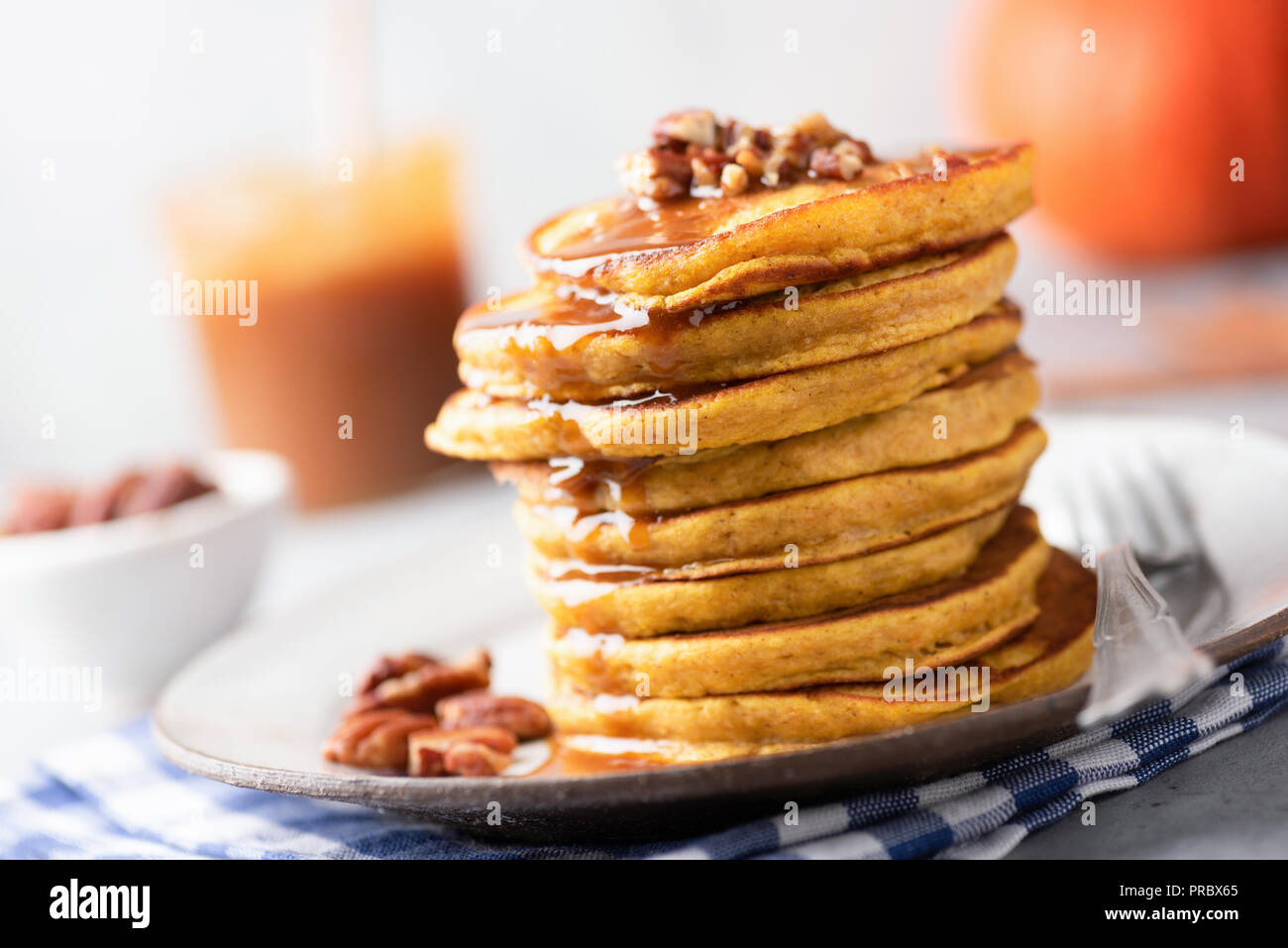 Tasty pumpkin pancakes with caramel sauce and nuts. Selective focus. Autumn comfort food, american Thanksgiving day breakfast - Stock Image