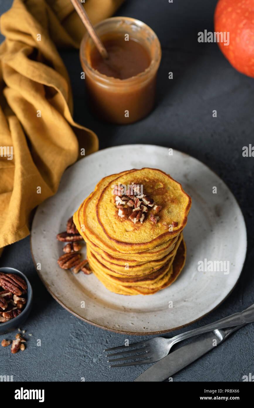 Pumpkin pancakes with caramel sauce and pecan on a plate. Top view, selective focus. Tasty pancakes autumn comfort food - Stock Image
