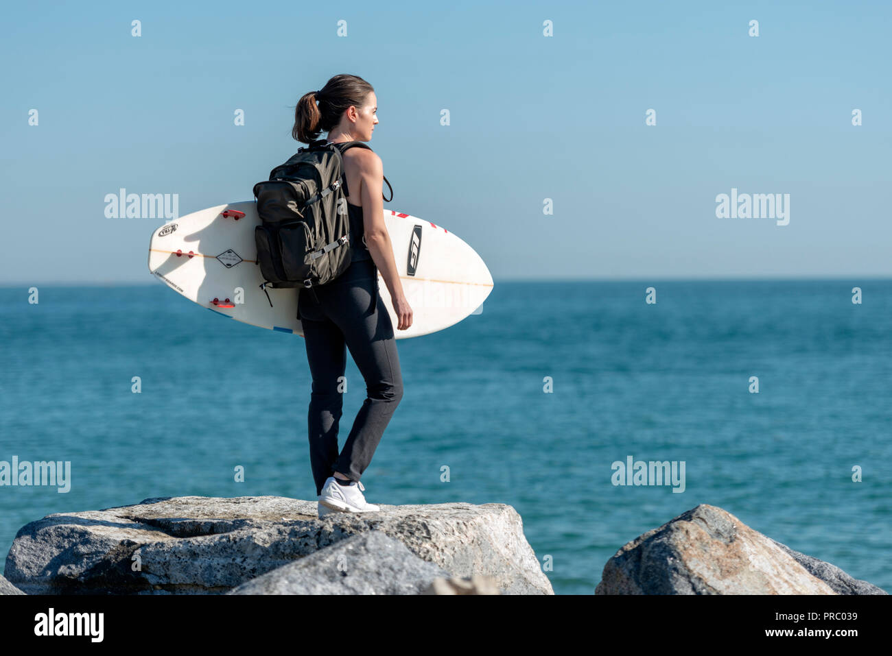 woman standing on rocks holding a surfboard checking out the sea before surfing. Stock Photo