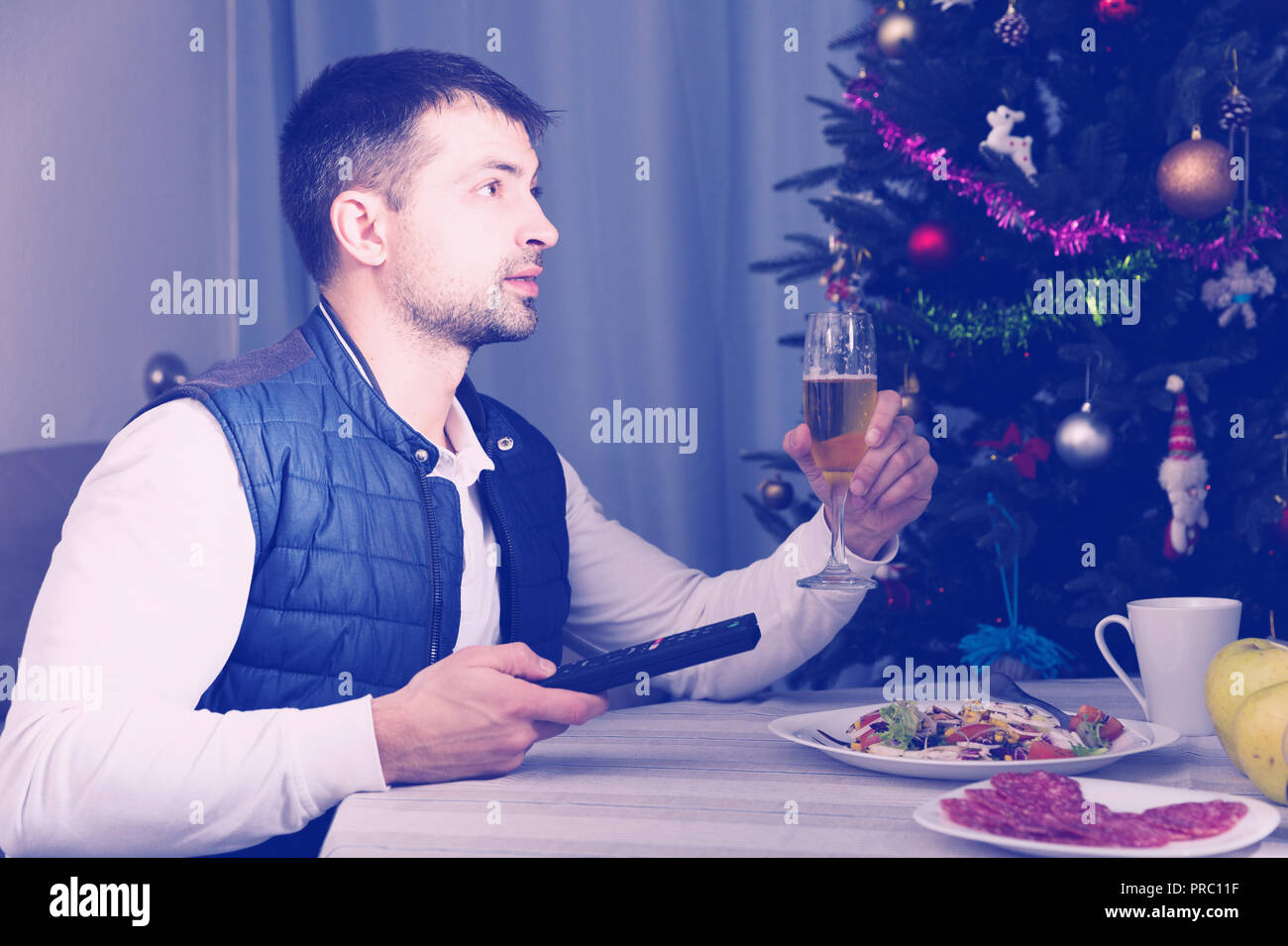 Man having christmas dinner with champagne and watching tv at home - Stock Image