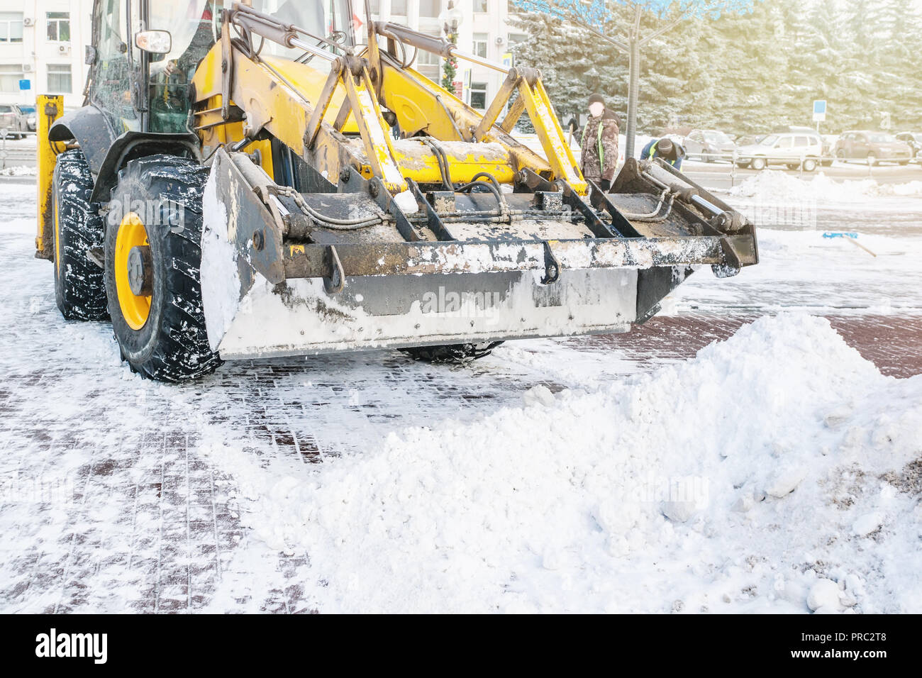 Yellow bulldozer clears the street after a heavy natural snowfall. Preparing for Christmas. Sunny frosty day. Close-up Stock Photo