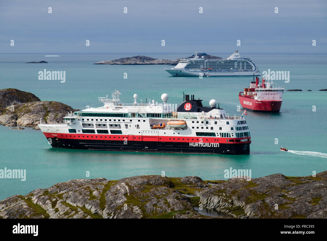 Royal Arctic Line container ship sailing passed visiting cruise ships MS Fram and Seven Seas Voyager anchored in Kuannersooq Fjord. Paamiut Greenland - Stock Image