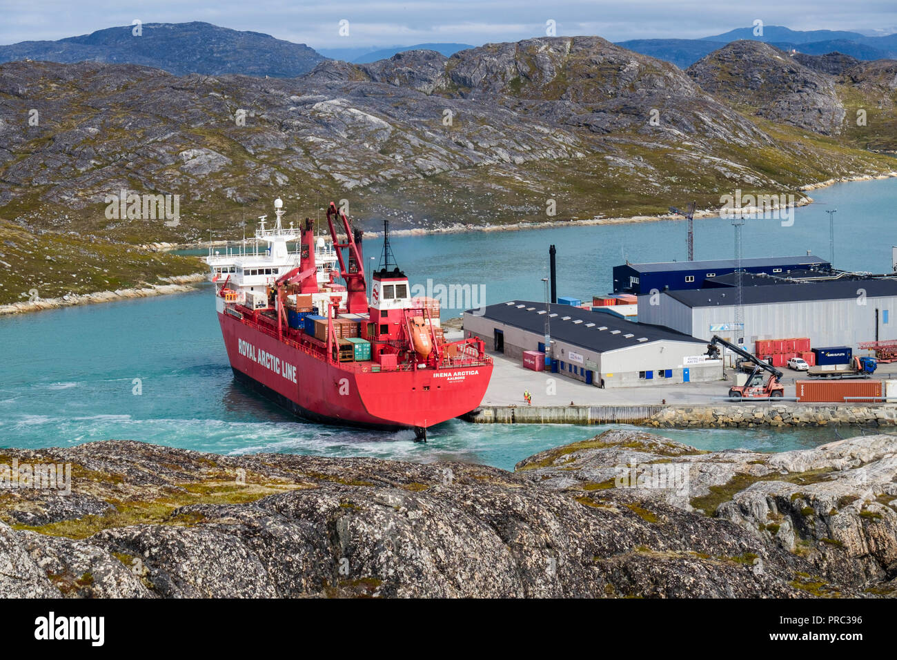 Royal Arctic Line container ship Irena Arctica (424 TEU) docked in port in fjord. Paamiut (Frederikshåb), Sermersooq, southwestern Greenland. Stock Photo