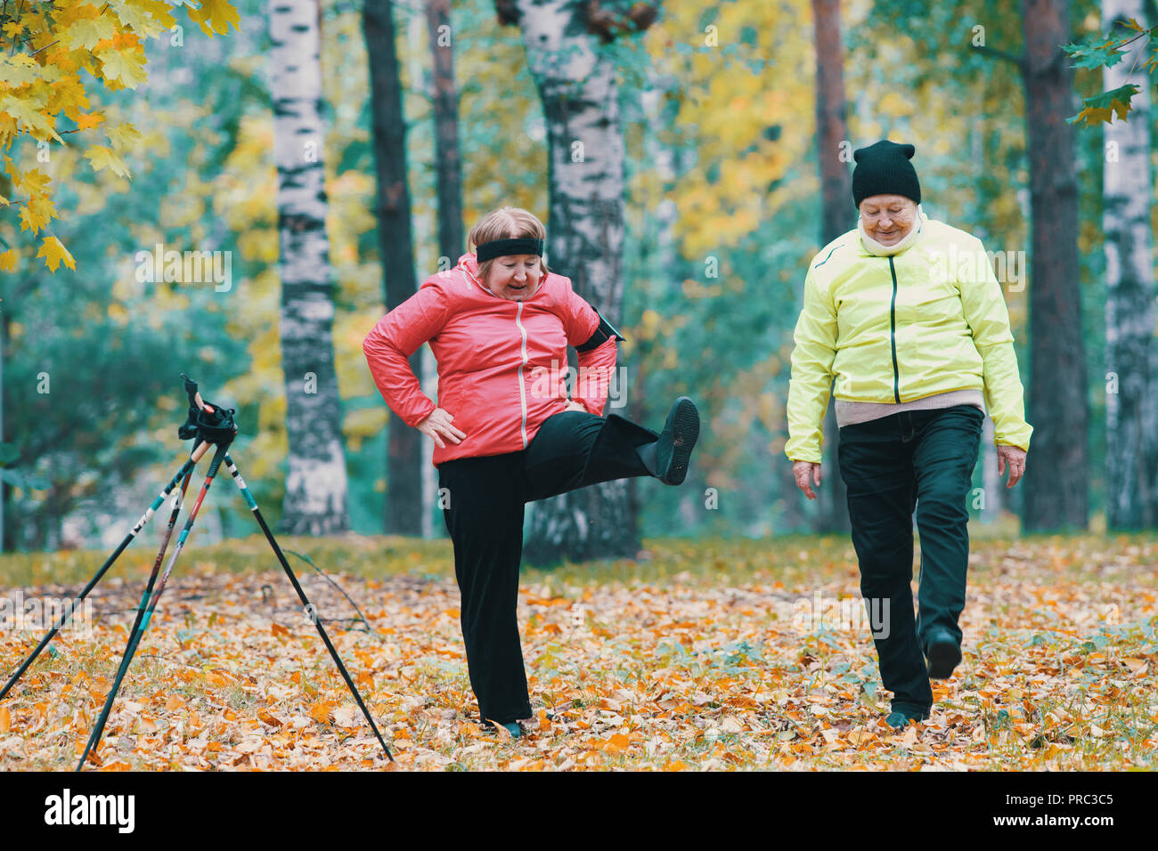 Mature woman performing a leg warm-up in an autumn park after a scandinavian walk - Stock Image