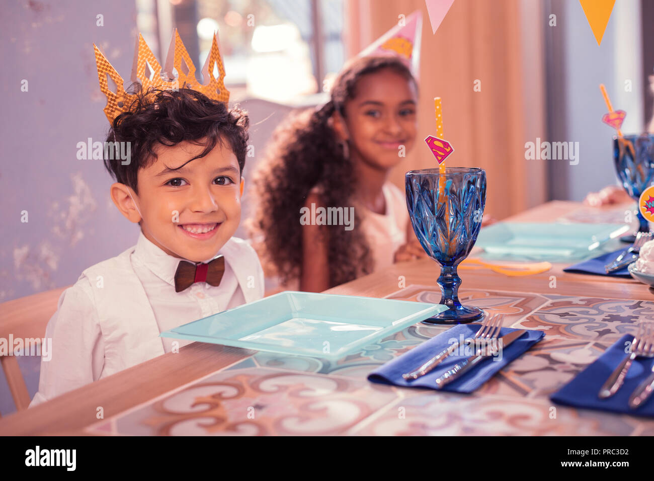 dea49db54457f Happy boy wearing paper crown and smiling while sitting Stock Photo ...