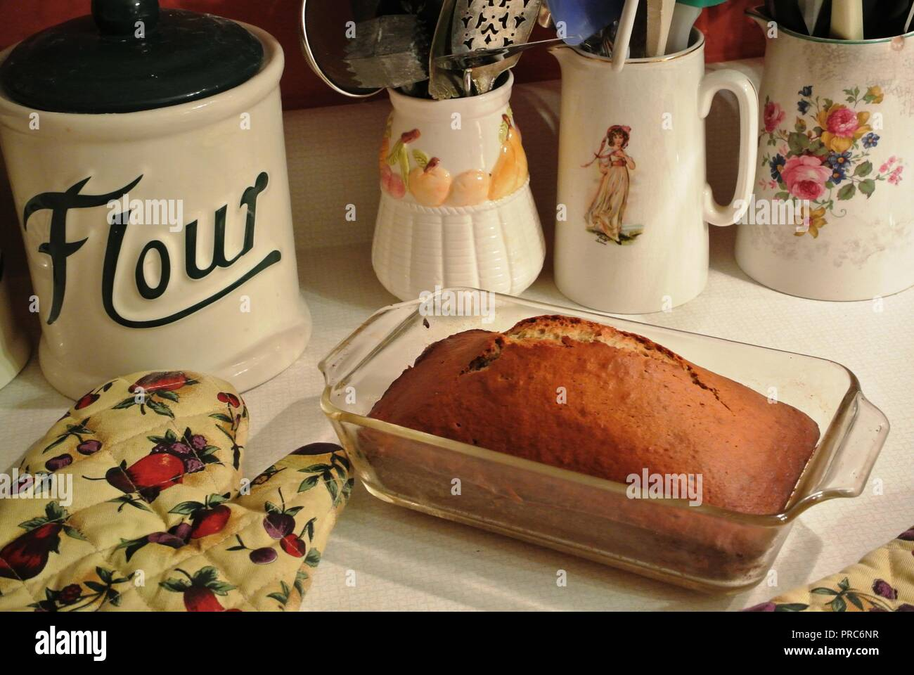 Freshly baked  loaf of a banana bread in a glass container surrounded by a colorful kitchen mitt, flour pot and utensils, warm ambiance, baking & cook - Stock Image
